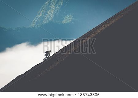 Silhouette of outdoor man climbing steep mountain.