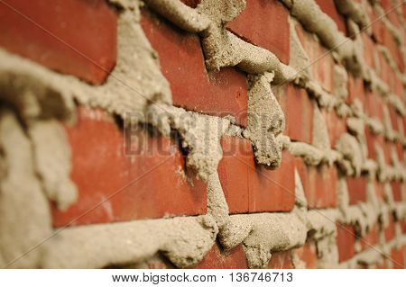 Brick wall conceptual image with spewing mortar
