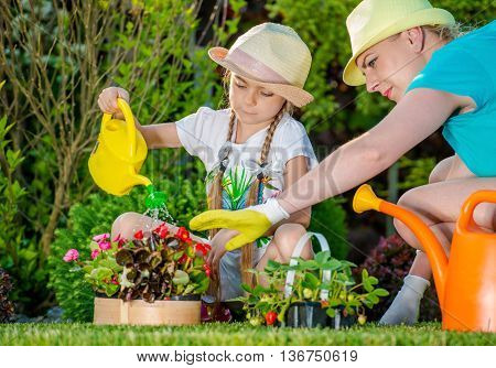 Mother and Daughter Working in Backyard Garden. Girl Learning How to Take Care of Garden Plants. Taking Care of Backyard Garden.