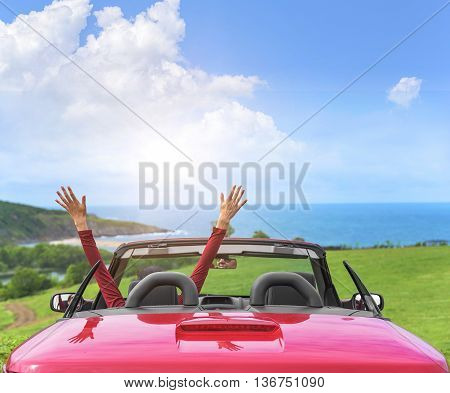 Girl in a red convertible car on a background seascape. poster