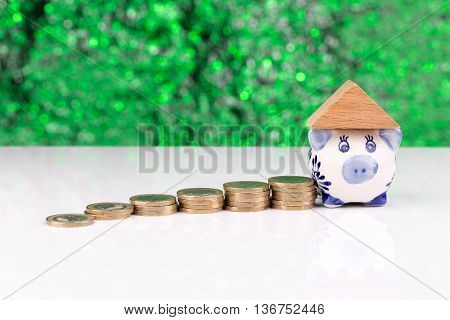 Wooden block houses and coin stacks in a row with a green background and a piggy bank