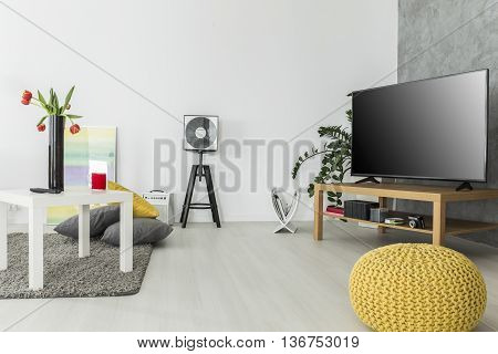 Modern living room with simple but trendy furniture and a tv set arranged in grey and yellow