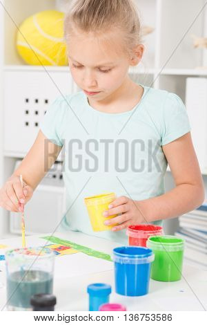 Shot of a focused little girl painting in her room