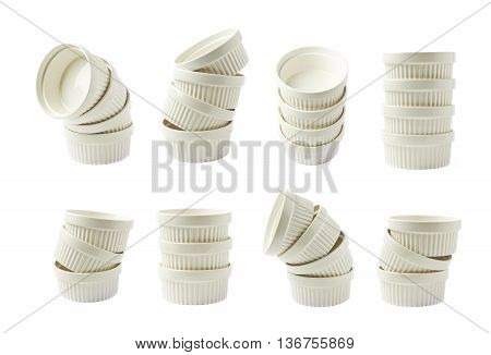 Pile of multiple white porcelain souffle ramekin dishes isolated over the white background, set of eight different foreshortenings