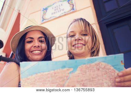 Female friends on holiday young latina women having fun traveling. Two happy girls smiling in Havana Cuba using city map for directions.