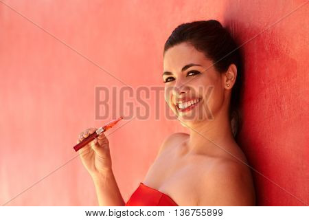 Young hispanic people smoking e-cig pretty sensual latina woman with electronic cigarette happy sexy girl smiling and leaning on red wall with copy space. Portrait looking at camera