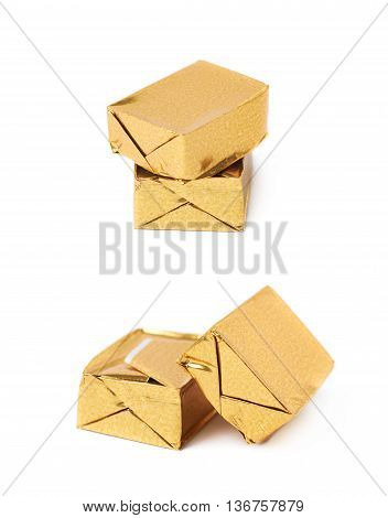 Pair of bouillon stock broth cubes wrapped in golden foil, composition isolated over the white background, set of two different foreshortenings