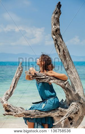 attractive young beautiful girl sitting on snag on beach