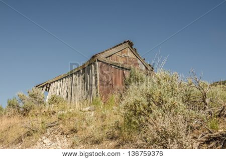 Weathered and dilapidated building with a curving wall that must have been green at one time