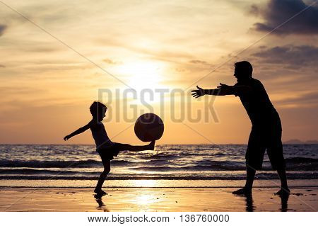 Father and son with ball playing soccer on the beach at the day time. Concept of friendly family.