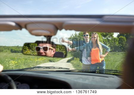 road trip, hitchhike, travel, gesture and people concept - happy couple hitchhiking and stopping car at countryside road