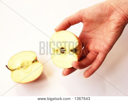 A Women'S Hand Holding The  Part  Of A Cut Apple
