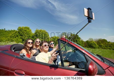 leisure, road trip, travel and people concept - happy friends driving in cabriolet taking picture by smartphone selfie stick at country