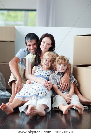 Happy famiy lying on floor after buying house