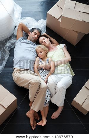 Famiy lying on floor with a lot of boxes after buying house