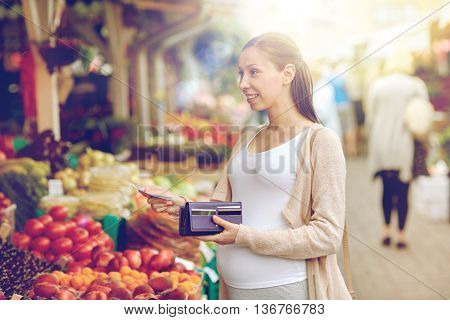 sale, shopping, pregnancy and people concept - happy pregnant woman with wallet and money buying food at street market