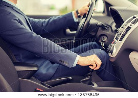 transport, business trip, speed, destination and people concept - close up of young man in suit driving car