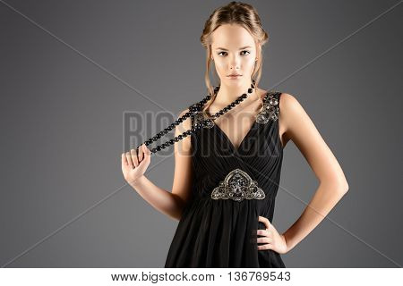 Pretty young woman in little black dress. Beauty, fashion. Studio shot.