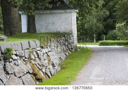 an old stone wall at the cemetary poster