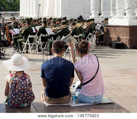 MOSCOW, RUSSIA - May 28, 2016: A pre-adolescent girl and a pair of young men seated on the parapet during a performance of the brass band. Central Avenue in the Park of VDNH Moscow. International Military Music Festival