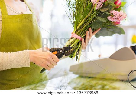 people, business, sale and floristry concept - close up of florist woman making bunch and cropping stems by pruner at flower shop