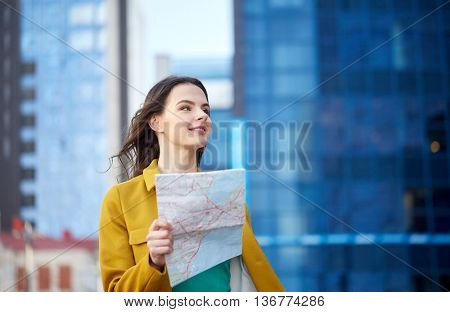 travel, trip, tourism, people and vacation concept - happy young woman with map walking along city street