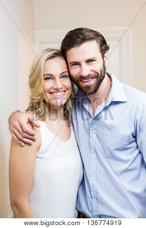 Happy couple standing with arm around at home