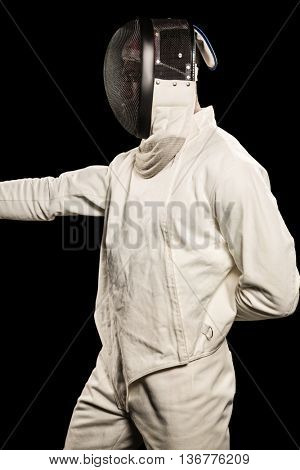 Man wearing fencing suit practicing on black background