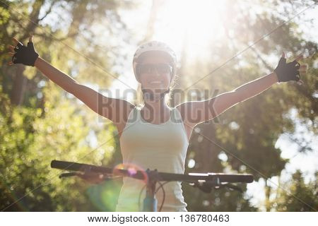 Woman rider smiling and throwing arms on the wood