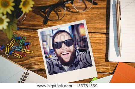 Happy hipster against wooden fence against high angle view of office supplies on table