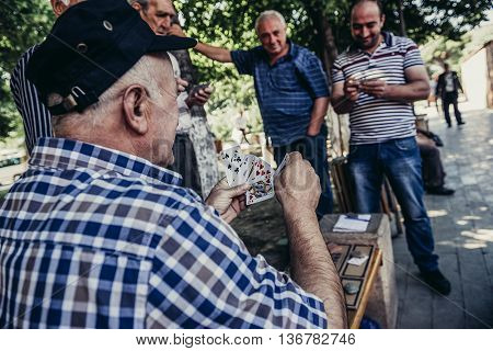 Tbilisi Georgia - July 18 2015. Georgian men plays card in small public park in Tbilisi