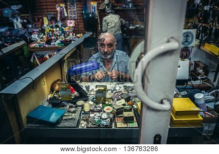 Tbilisi Georgia - July 18 2015. Man works in traditional clockmaker workshop in Tbilisi