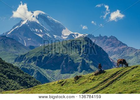 Gergeti Georgia - July 20 2015. Tourist sits on a rock view with Kazbek Mountain near Gergeti village in Caucasus Mountains Georgia