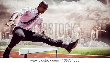 Businessman jumping a hurdle against composite image of track against city