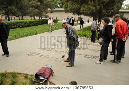 Temple of Heaven Park Beijing China. April 26 2016.  A chinese man writing a poem in Chinese characters with water on a sidewalk within the Temple of Heaven Scenic area in Beijing China.