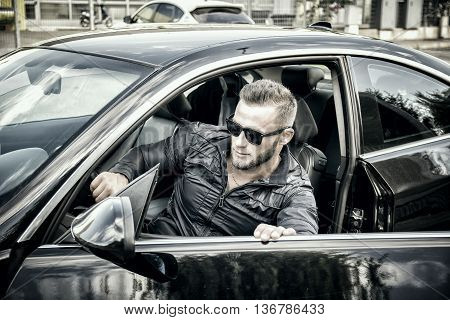 Portrait of young bearded man in sunglasses getting out of his new stylish polished car outdoor