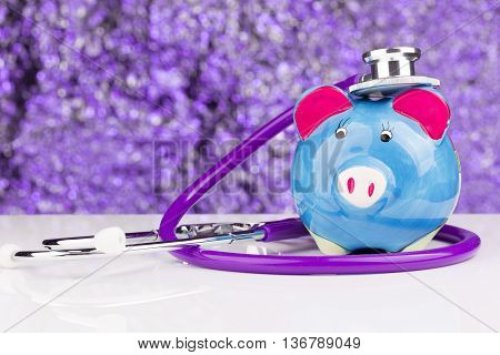 Close up of a stethoscope with a piggy bank
