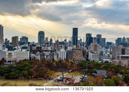 Osaka city skyline with a park in the foreground.  Construction work is being completed in the park.