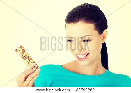 Young woman eating Cereal candy bar