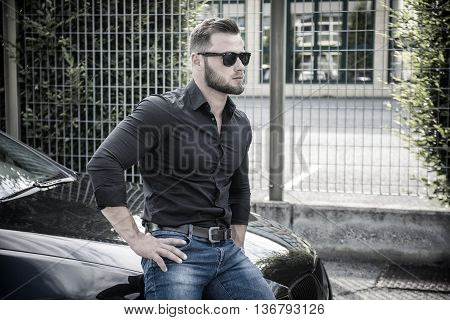 Portrait of young bearded man in sunglasses leaning on his new stylish polished car, outdoor