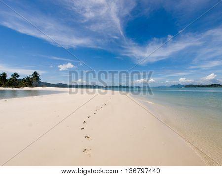 Footprints in the sand along beach on heavenly island