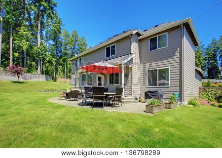 Large Back Yard With Concrete Patio Area And Well Kept Lawn.