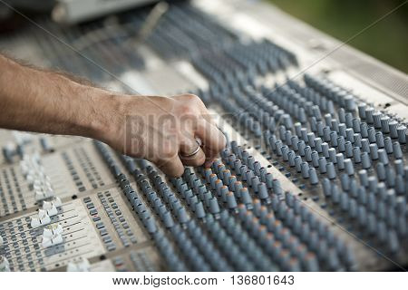 DJ hand over an audio mixing console.. Deejay adjusting audio mixer.