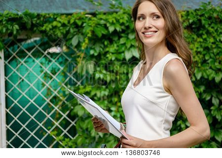 Young businesswoman holding documents in park outdoors