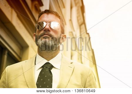 portrait of businessman standing in the street wearing sunglasses
