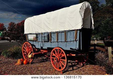 Intercourse Pennsylvania - October 13 2015: A Pennsylvania conestoga covered wagon with autumn pumpkins and gourds at Kitchen Kettle Village