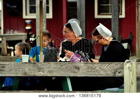 Intercourse Pennsylvania - October 13 2015: Two Mennonite women with children having a snack in the children's playground at Kitchen Kettle Village