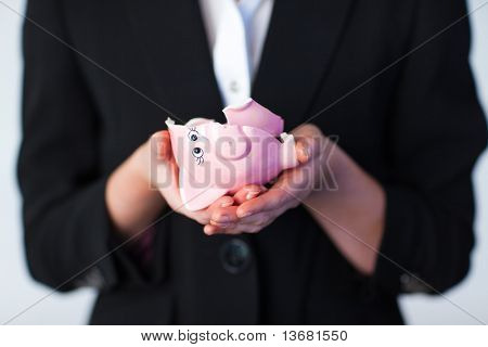 Young Business woman holding a broken piggy bank