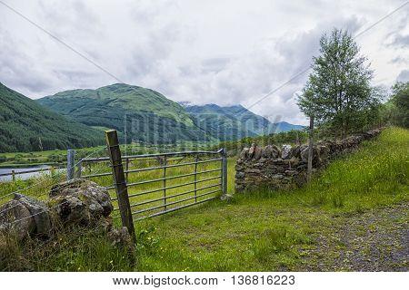 Modern metal farm gate set in traditional dry stone wall beside Loch Doine Scotland