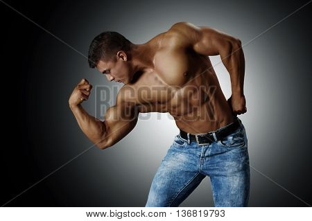 Handsome muscular man in blue jeans, showing his biceps. Black background.